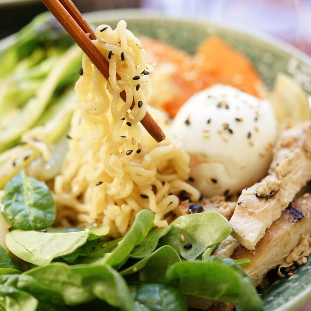 Ramen Noodle Recipe in bowl served with chopsticks, topped with a soft boiled egg.