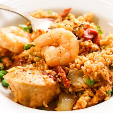 Seafood and chicken Paella in bowl with fork.