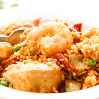 Slow Cooker Paella in white bowl with fork.