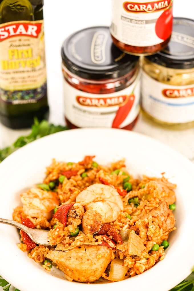 Slow Cooker Paella in a white bowl with fork surrounded by ingredients.