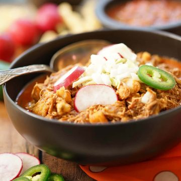 Authentic Posole Recipe in black bowl topped with onions, jalapeños and sliced radishes.