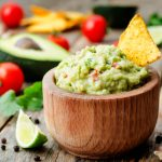 guacamole with corn chips on a dark wood background.