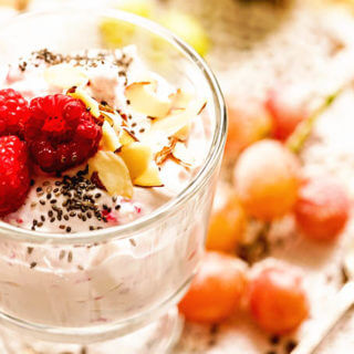 Glass parfait glass filled with yogurt and topped with raspberries.