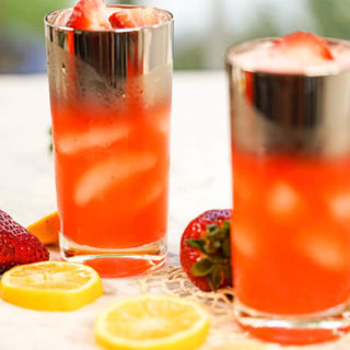 Two glasses filled with strawberry lemonade, garnished with lemons and strawberries!