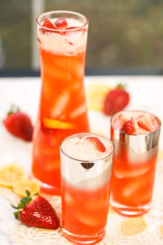 Glasses Homemade Strawberry Lemonade on white board with strawberries and lemon slices.