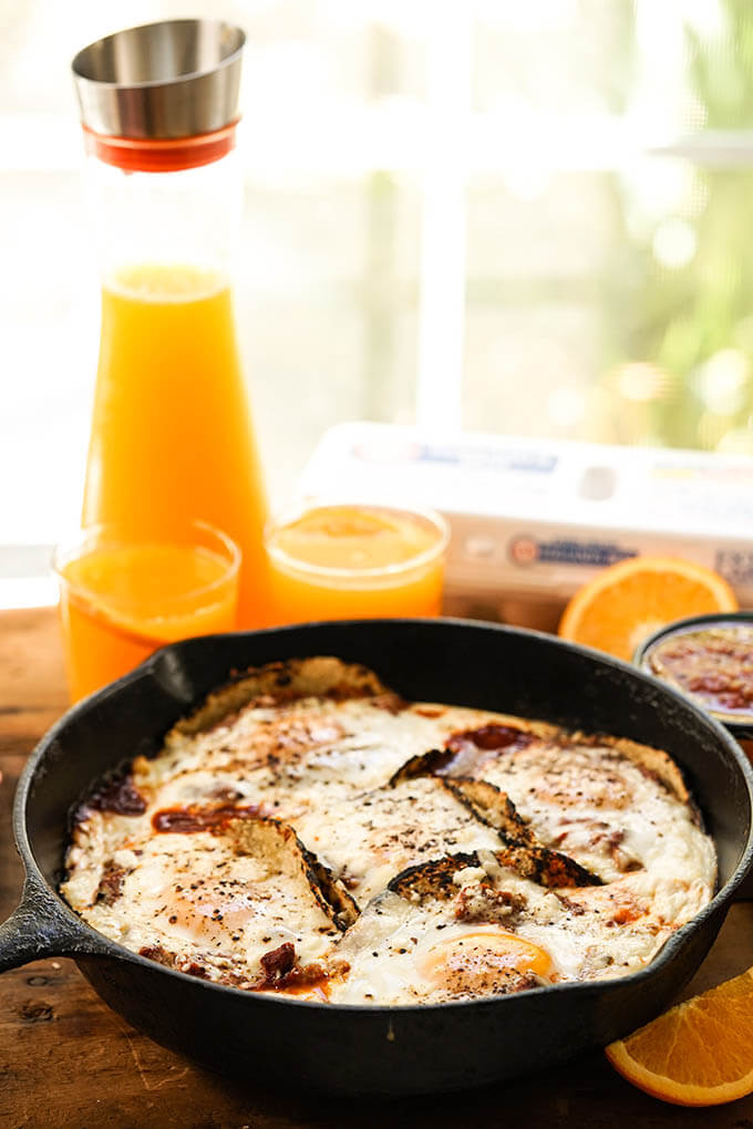 Easy Huevos Rancheros Recipe in cast iron skillet with orange juice.