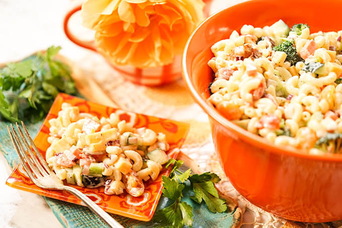 Macaroni Pasta Salad Recipe in orange bowl with a serving on a plate with fork.
