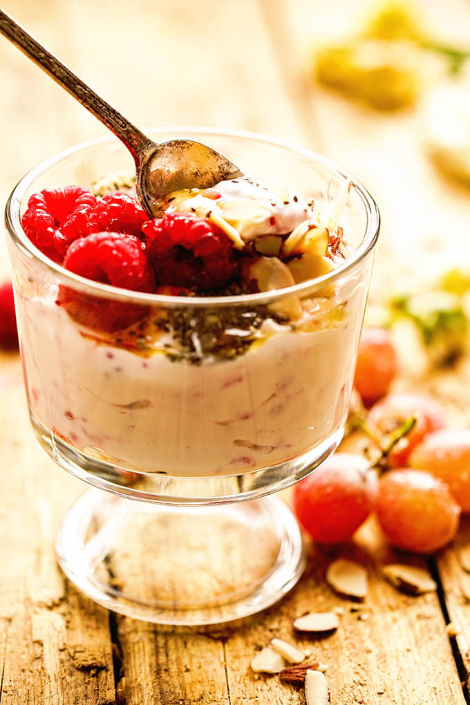 Easy make ahead breakfast parfait topped with nuts and raspberries.