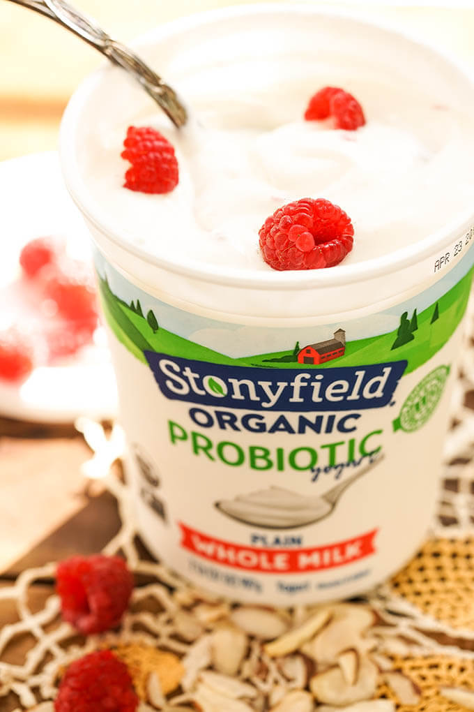 A quart of plain yogurt topped with raspberries.