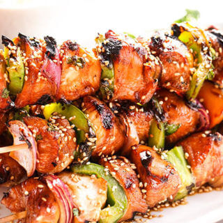 Teriyaki Chicken Kabobs garnished with sesame seeds on white platter.