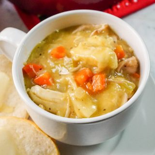 Easy Chicken and Dumpling Soup in white bowl with biscuits.