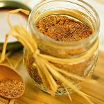 Homemade pork rub in mason jar with wooden measuring spoon on the side.