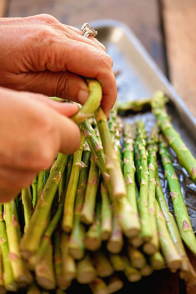 A brunch of asparagus on a sheet pan. The end of one stalk is being snapped off.