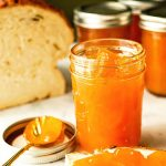 Jars of apricot jam spread on fresh bread.