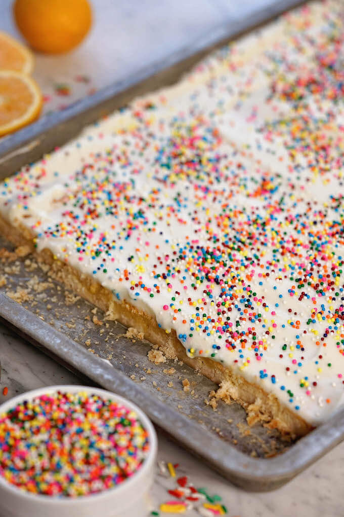 Lemon Bars in sheet pan with a bowl of sprinkles