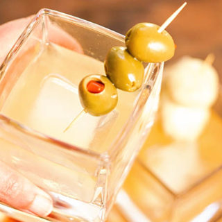 A glass hold a cocktail garnished with mushrooms and olives.