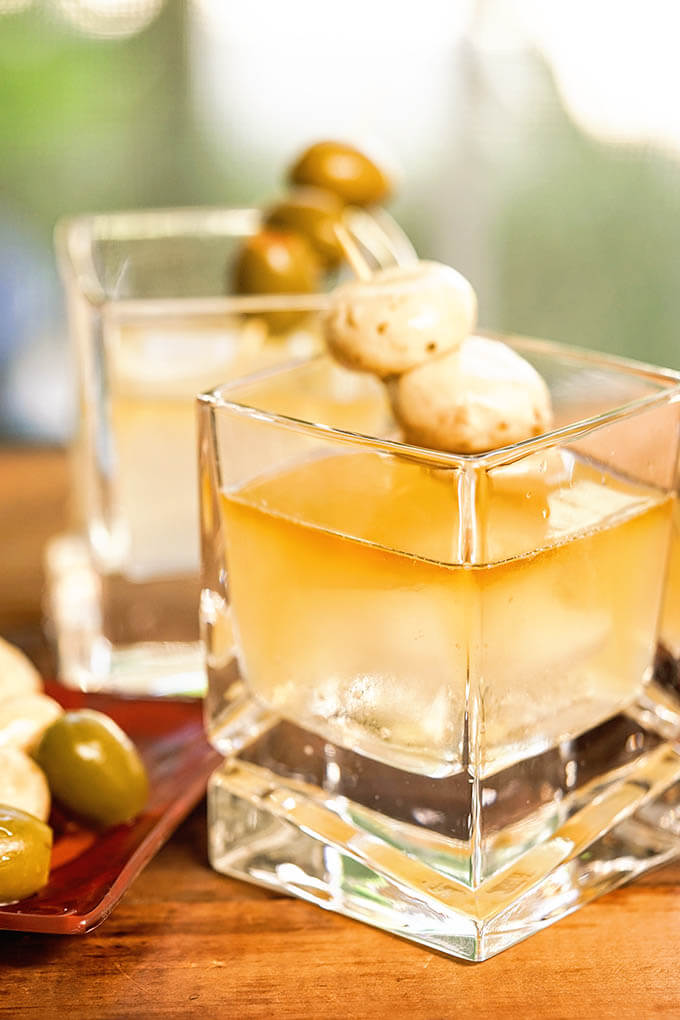 Two cocktails filled with Whiskey Old Fashioned Sour garnished with mushrooms and olives.