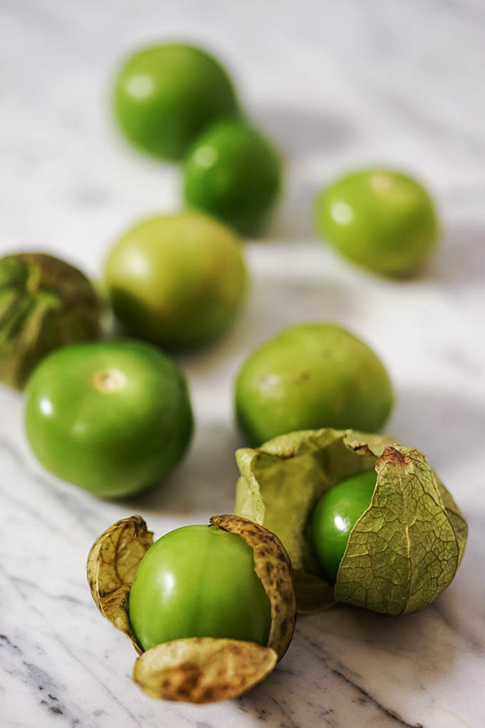 Tomatillos on marble counter.