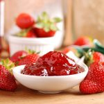 Strawberry Freezer Jam in white bowl surrounded by strawberries