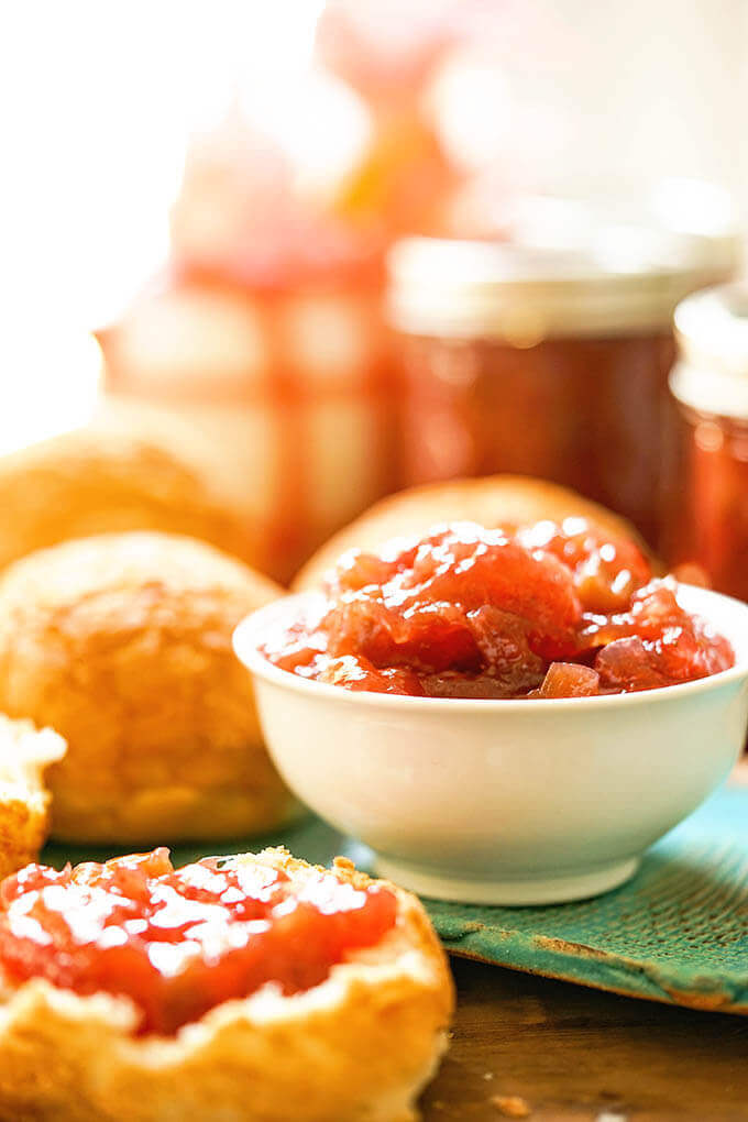 Strawberry Rhubarb Jam in white bowl and spread on bread.