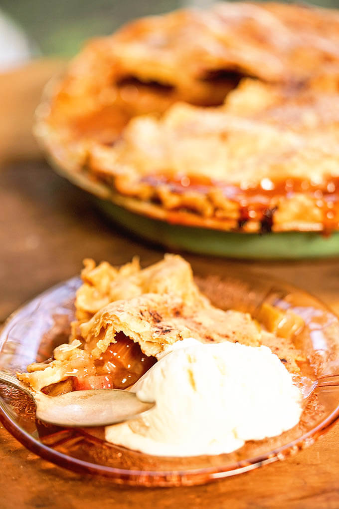 Fresh Rhubarb Pie with a slice of pie and vanilla ice cream.