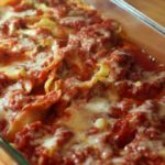 Stuffed shells with sauce in clear casserole pan