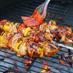 Korean BBQ chicken grilled on hot coals being basted with sauce.