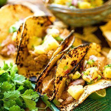 How to make Tacos al Pastor - tacos on blue platter with salsa.