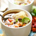 Soup in white bowl topped with jalapeños, diced tomatoes and tortillas