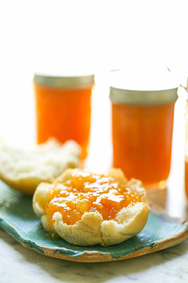 Apricot Pineapple Preserves spread on a roll on plate with jars of preserves.