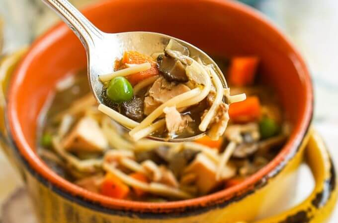 Directions for how to make chicken noodle soup from scratch. Soup in a yellow bowl with spoon.