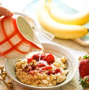 Oatmeal in bowl with strawberries topped off with milk