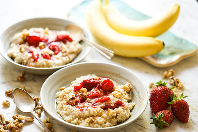Instant Pot Steel Cut Oats in bowls topped with strawberries and nuts.