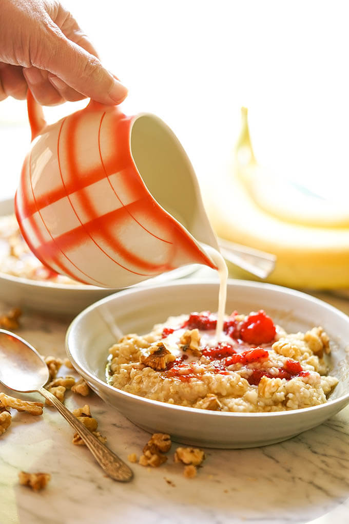 Oatmeal with strawberries in bowl. Milk is poured in from pitcher.