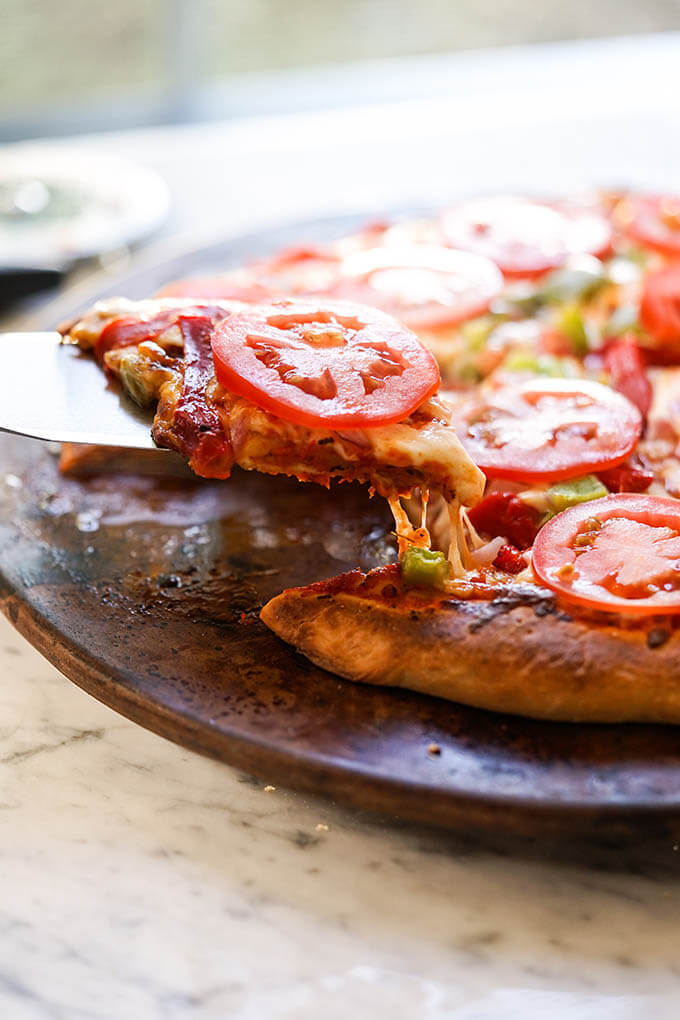 Baked pizza topped with fresh tomatoes sliced and being served.