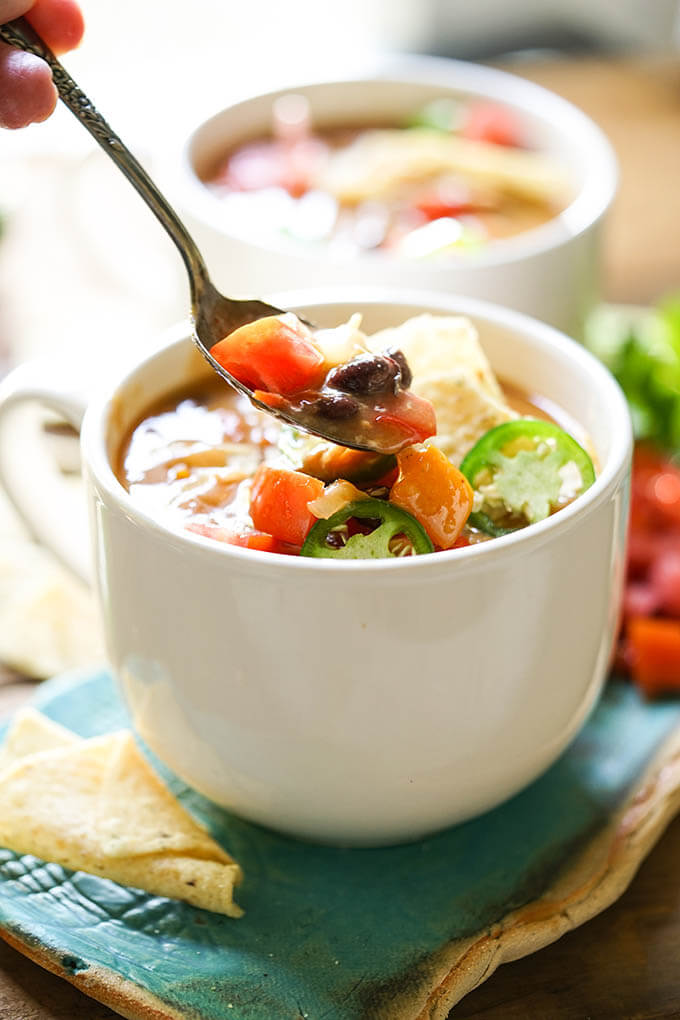 Bowls of slow cooker enchiladas soup with spoon