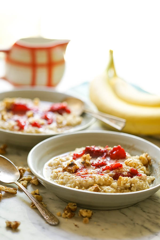 Instant Pot Steel Cut Oats in bowls with strawberries and milk.