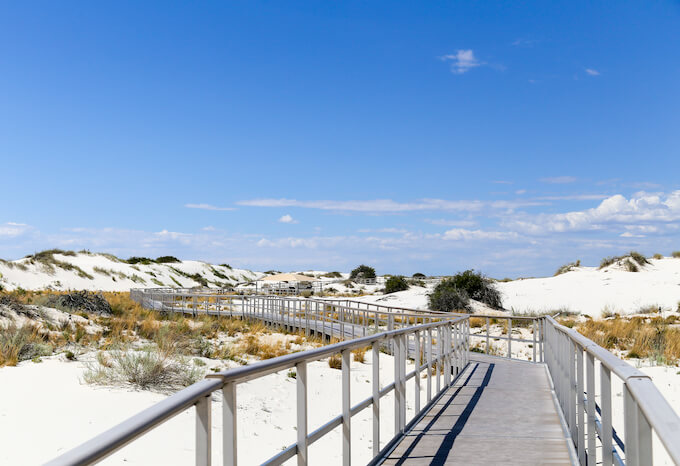 A boardwalk over the white sands preserving the National Monument.