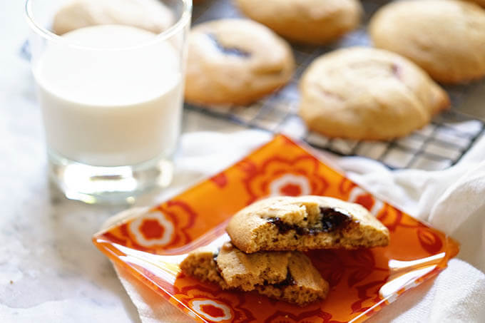 Cookie on orange plate with glass of milk
