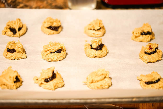 Cookies on baking sheet filled with jam and topped with more cookie dough.