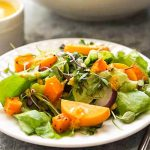 Fall Harvest salad with persimmons and roast squash on white plate with fork.