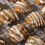 Persimmon cookies on cooling rack drizzled with white chocolate.