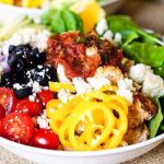 One Chicken Burrito Bowl filled with tomatoes, beans and vegetables.
