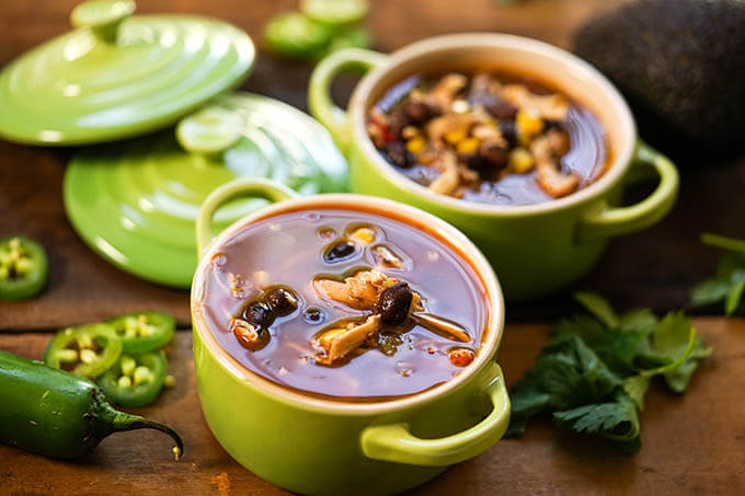 Chipotle Tortilla Soup in green bowls with sliced jalapeños.