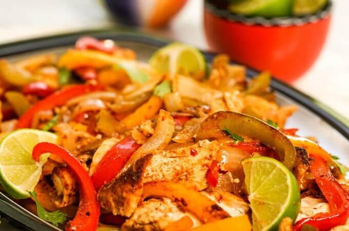Fajitas on pan with bowls of lime and jalapeños on the side.