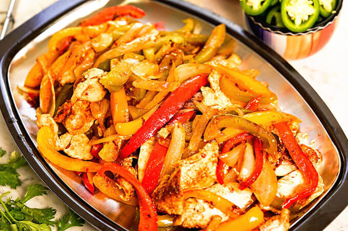 Cooked chicken Fajitas on platter.