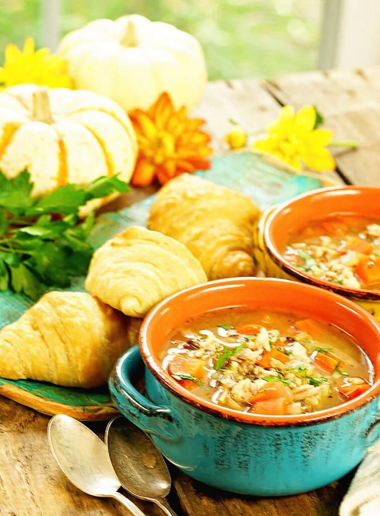 Two bowls of leftover turkey and wild rice soup with croissants