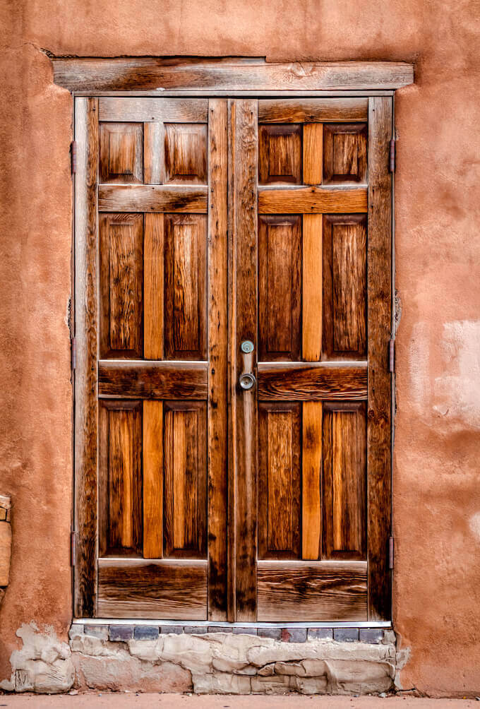 Beautiful carved wooden door on pueblo home.
