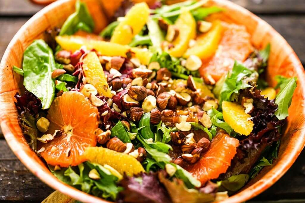 Bitter Green Salad topped with oranges and filbers.