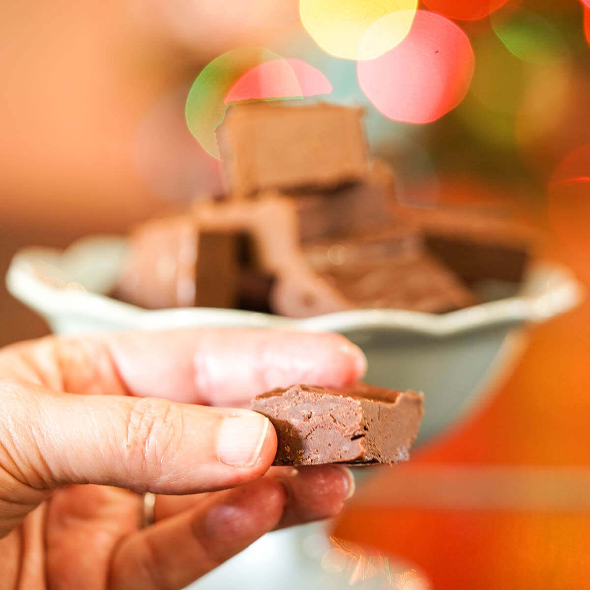 Fudge in green bowl with hand holding a piece - so chocolatey!